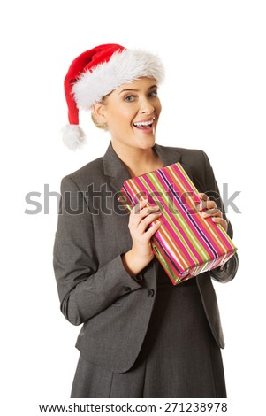 Woman weating Santa hat and holding a present. - stock photo