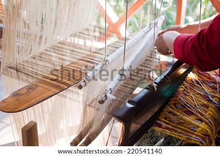 Woman weaving silk in traditional way at manual loom. Laos - stock photo