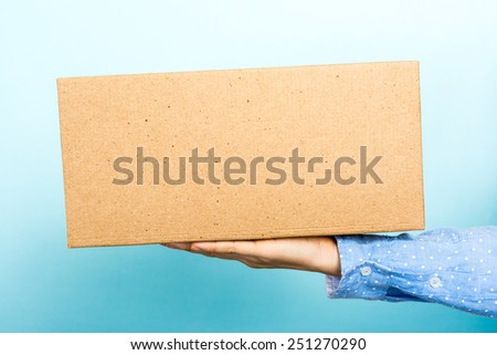 Woman weighing a cardboard box with her hand. Useful for announcing, shipping information, so on. - stock photo