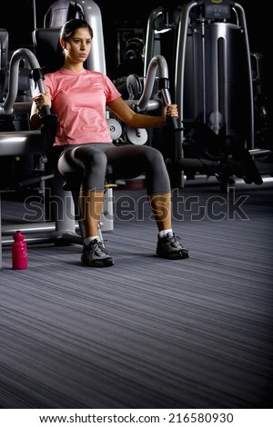 Woman weight lifting with exercise equipment in health club - stock photo