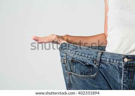 Woman weight loss by wearing and old jeans, close up - stock photo