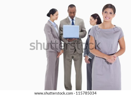 Woman welcoming and holding her hands and co-workers talking with a laptop in the background - stock photo