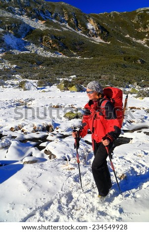 Woman while winter trekking on snow covered valley in sunny day - stock photo