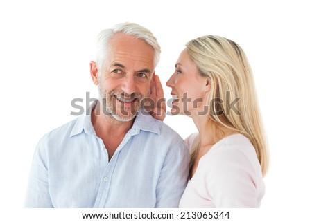 Woman whispering a secret to husband on white background - stock photo