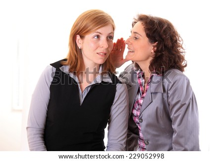 Woman whispering gossip in an other woman ear - stock photo