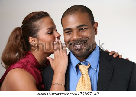Woman whispering in husband's ear. Closeup, shallow DOF, focus on man. - stock photo