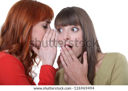 Woman whispering to her friend - stock photo