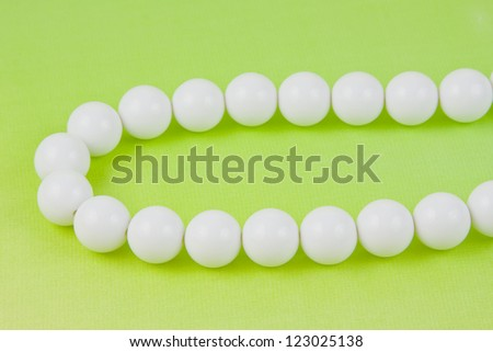 woman white beads on a light green background