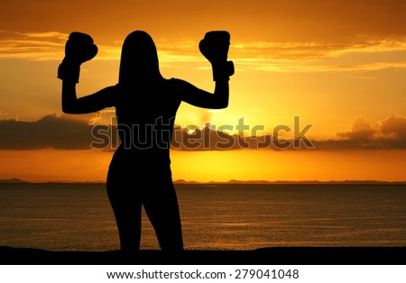 Woman who is working out on the beach with a sunset - stock photo