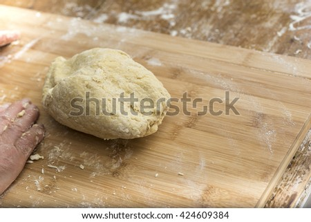 Woman who kneads the homemade pasta to prepare lasagna and tagliatelle. Italian cooking - stock photo