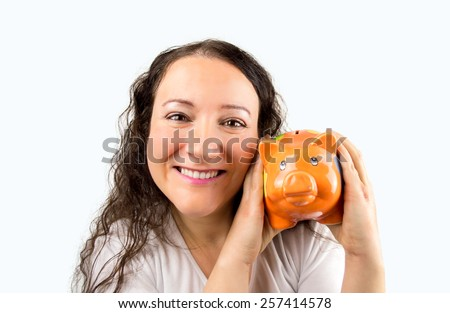 woman who loves her piggy bank savings with an orange pork - stock photo