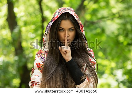 Woman wide eyed asking for silence or secrecy with finger on lips hush hand gesture green background wall. Pretty girl placing fingers on lips, shhh sign symbol. Negative emotion facial expression - stock photo