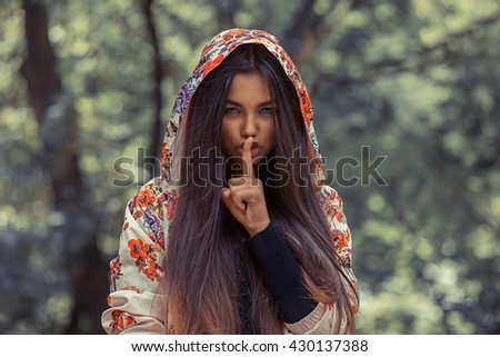 Woman wide eyed asking for silence secrecy with finger on lips hush hand gesture  isolated green background wall Pretty girl placing fingers on lips shh sign symbol. Negative emotion facial expression - stock photo