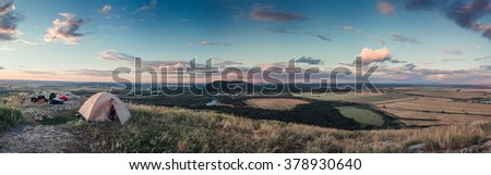Woman wild camping on grassy mountain top - stock photo