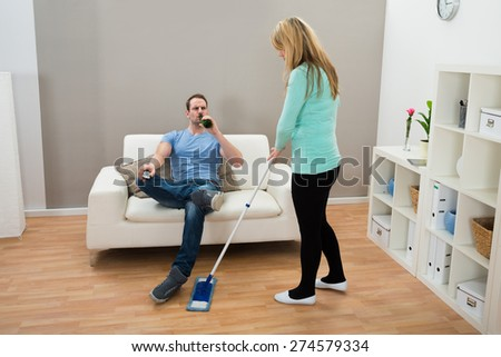 Woman Wiping Floor While Man On Sofa Drinking Alcohol