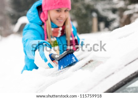 Woman wiping snow car window using brush winter happy work