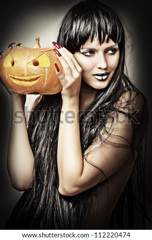Woman witch with black hair with pumpkin - stock photo