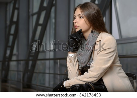 Woman with a bag in her lap in waiting for departure on the background of metal structures in the waiting room