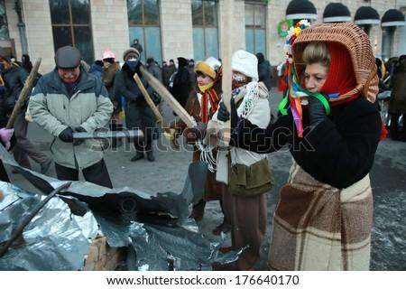 Woman with a basket on her head on metal bats. Kyiv, Ukraine, January 20, 2014 - stock photo
