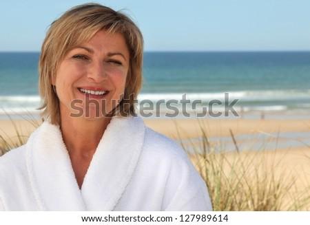 Woman with a bathrobe on the beach - stock photo