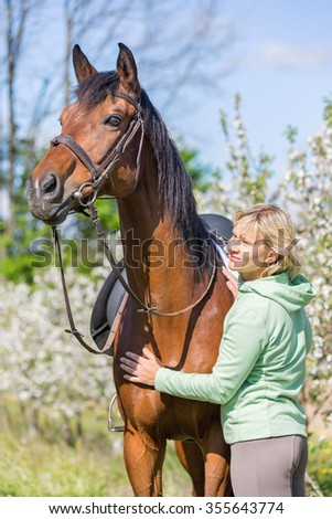 Woman with a bay horse in blooming apple orchard.