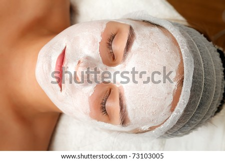 Woman with a beauty mask on her face in a salon - stock photo