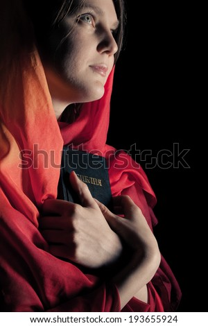 Woman with a Bible in the night. Isolated on a black background - stock photo
