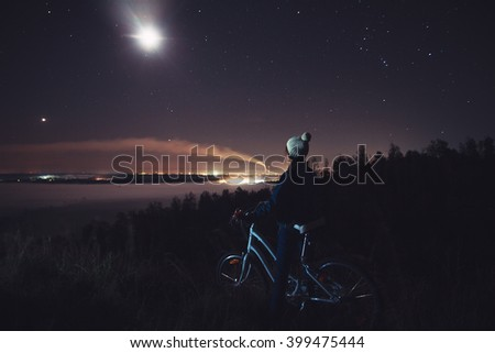 Woman with a bicycle on the background of foggy valley. Girl enjoys beautiful scenic view. Valley in the mist and moonlight.  Valley filled with fog. Fumes from power plants scatters on the sky. - stock photo