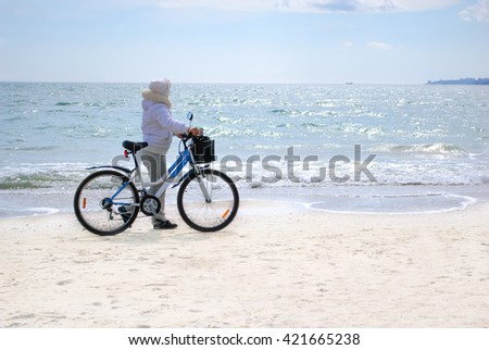 woman with a bicycle on the beach  - stock photo
