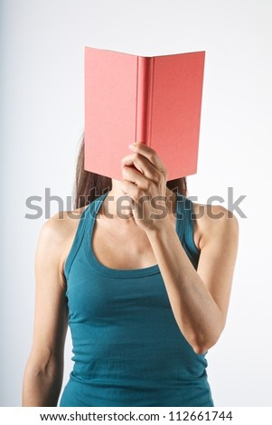 woman with a book in her face on white background - stock photo