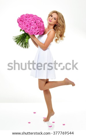 Woman with a bouquet of roses. Blonde with pink flowers. - stock photo