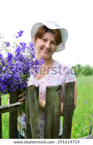 Woman with a bouquet of wildflowers near the wooden fence in the village