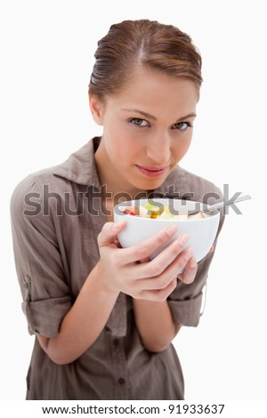 Woman with a bowl of fruit salad against a white background