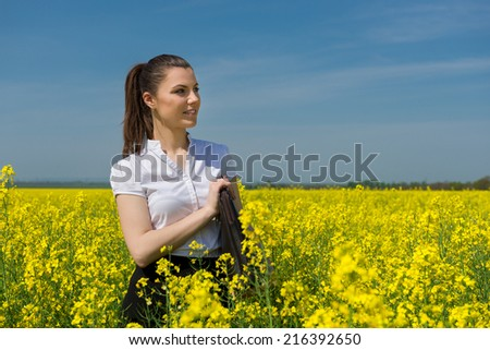 woman with a briefcase on yellow flower field - stock photo