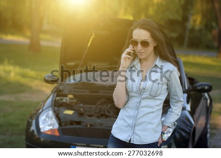 Woman with a broken down car - stock photo
