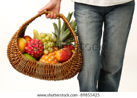 Woman with a cane basket of fruit in the hand - stock photo