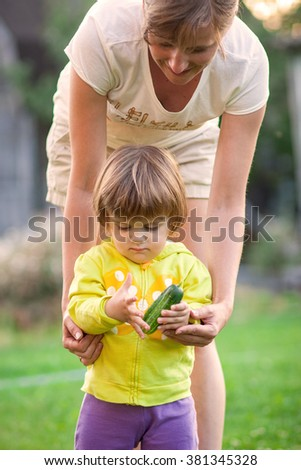 woman with a child pick vegetables. - stock photo