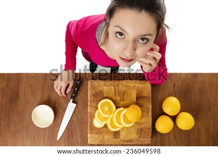 woman with a chopped up a orange layed out on a wooden chopping board taken from a birds eye view looking down - stock photo