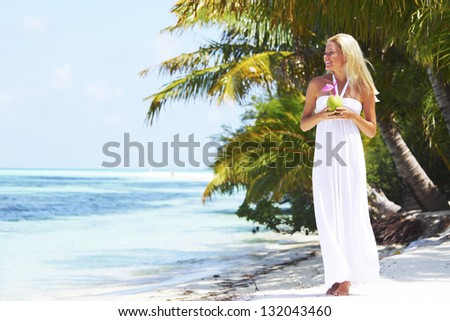 woman with a coconut cocktail on a tropical shore - stock photo