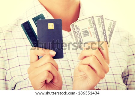 Woman with a credit card and cash on her hand - stock photo