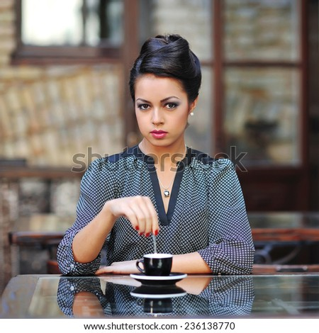 Woman with a cup of coffee at the cafe - stock photo