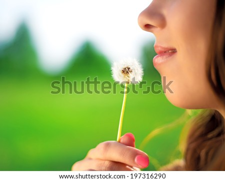 woman with a dandelion outdoor in the summer park, closeup, focus on the lips - stock photo