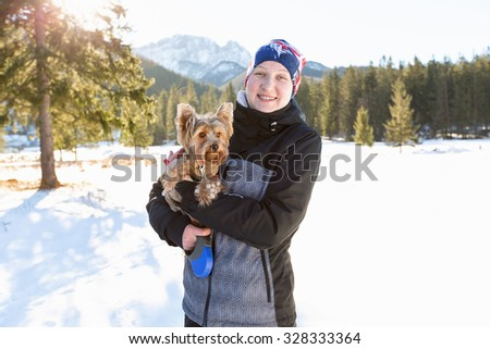 Woman with a dog on a walk in the winter. Girl with a Yorkshire terrier against a background of high mountains in winter on a sunny day.