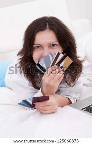 Woman with a fistful of credit cards lying on her bed with her laptop browsing online for something to purchase