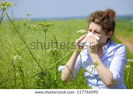 Woman with a flu or an allergy sneezing into her handkerchief in spring - stock photo