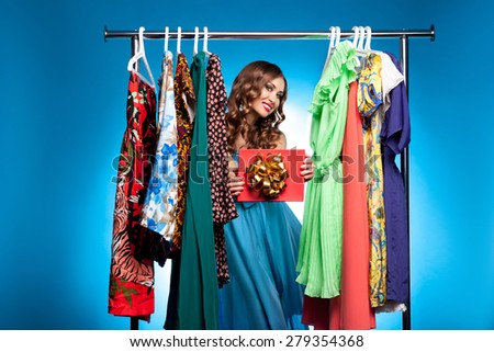 Woman with a gift at the counter with the clothes on a blue background - stock photo