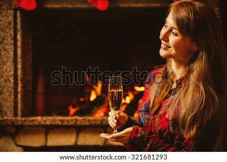 Woman with a glass of champagne by the fireplace. Young woman sitting by the fireside and holding a wineglass with shimmer wine, enjoying cozy evening in chalet. Holiday Christmas time concept.