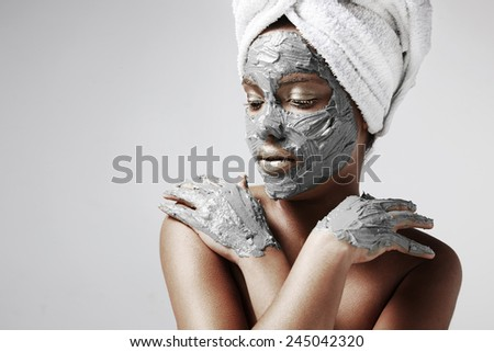woman with a grey facial mask on her face and hands - stock photo