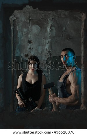 Woman with a gun and a man with a big hammer, they are terrorists. - stock photo