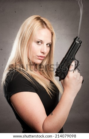 woman with a gun on gray background - stock photo